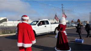 Santa and Mrs. Claus waving to truck with American flags image